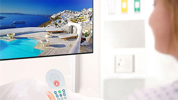 Hospitality Hospital TV for patients with a patient using a remote control.